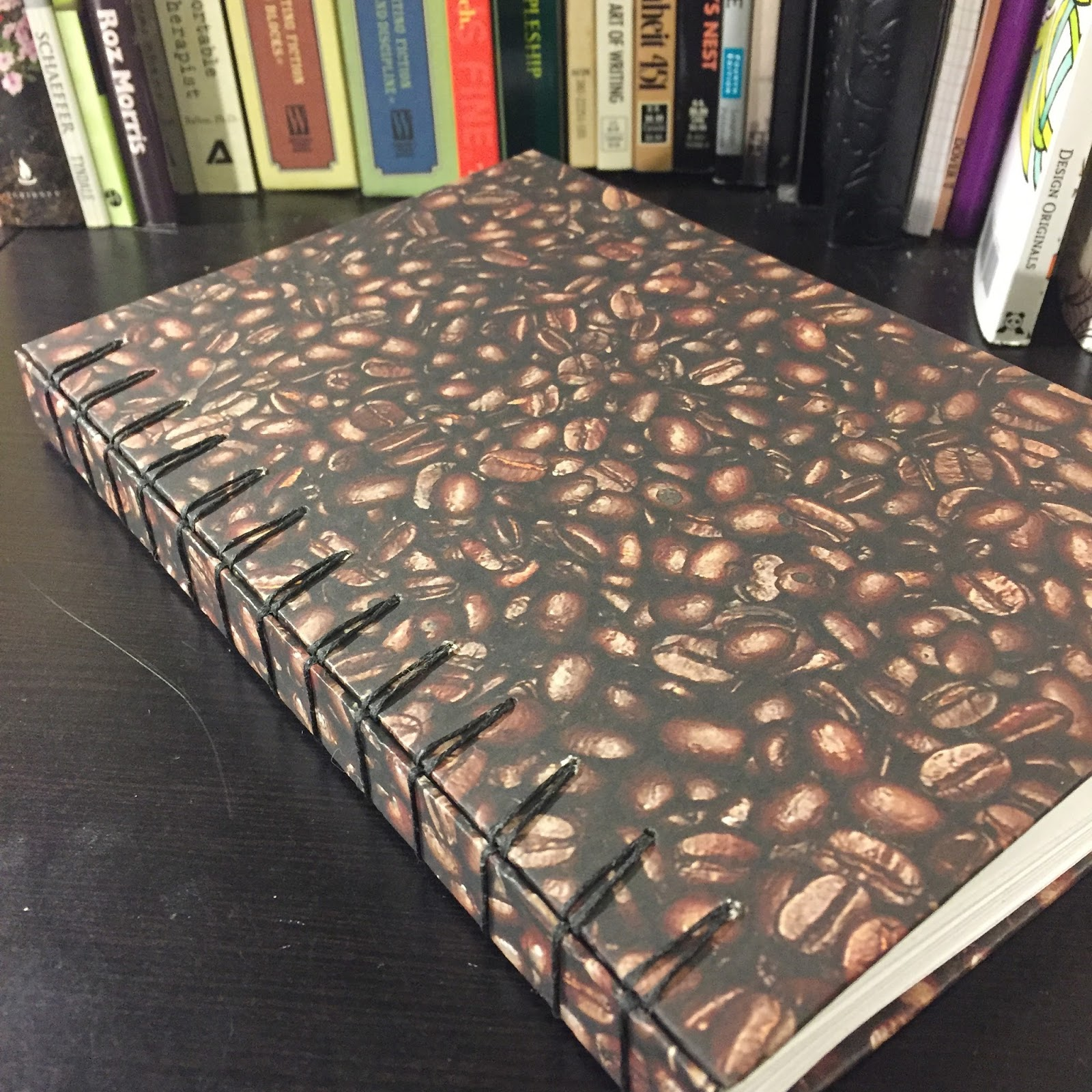 handbound journal with coffee beans on cover on black desk in front of bookshelf