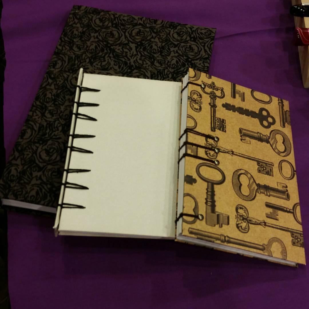 three handbound journals stacked next to each other on purple background
