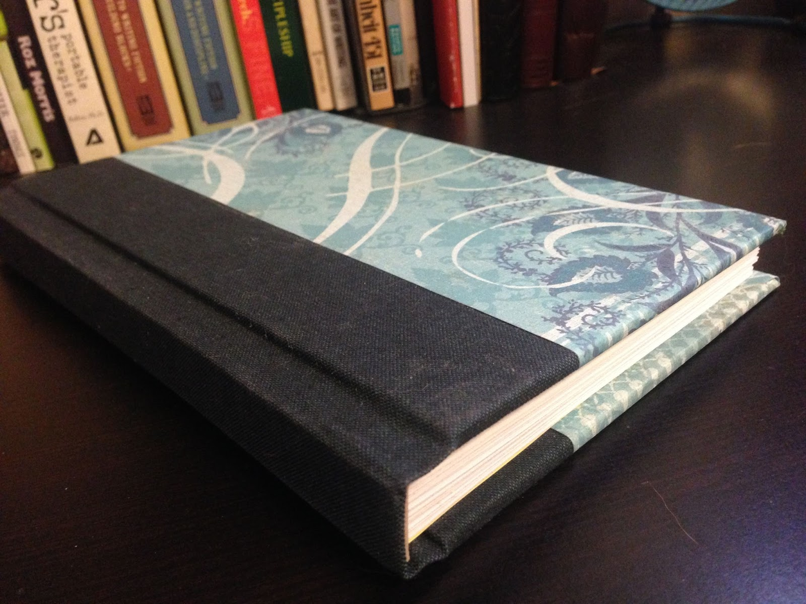 handbound journal with black spine and blue pattern print cover on black table next to bookshelf