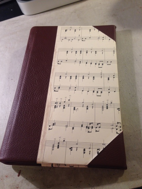 leather and music notes handbound brown and white journal on gray desk