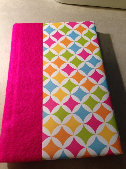 pink and geometric colorful handbound journal on gray desk